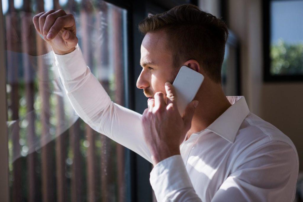 man smiling taking phone call